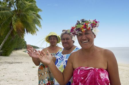 islanders: Portrait of Polynesian Pacific Island Tahitian mature females smiles and wave haloha, hellow,  on the beach in Aitutaki lagoon Cook Islands. Stock Photo