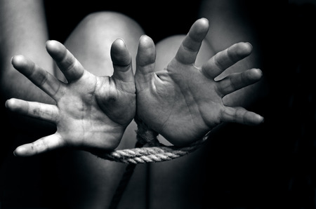 A missing kidnapped, abused, hostage, victim woman with hands tied up with rope in emotional stress and pain, afraid, restricted, trapped, call for help, struggle, terrified, threaten, locked in a cage cell try to escape.