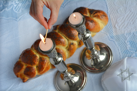 jewish home: Shabbat eve table.Woman hand lit Shabbath candles with uncovered challah bread and kippah. Stock Photo