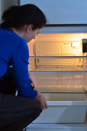 no food: Sad, hungry poor woman look for food in empty fridge at home. Stock Photo
