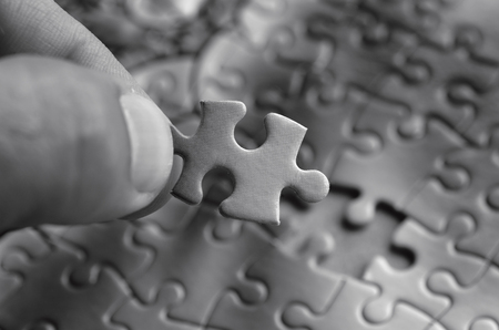final piece of puzzle: Hand holds the last puzzle piece.Business concept for completing the final puzzle piece (BW) Stock Photo