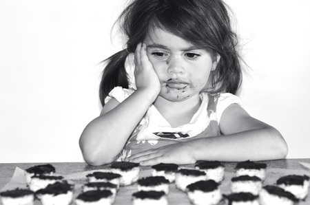 dispersed: Little girl wants to eat lots of chocolate cookies.Concept photo of Child,children,depression,dispersed, food, health care , diet, eating disorder,bulimia. (BW) copy space Stock Photo