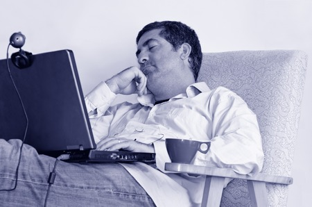 telework: Tired man that works from home sleeps in front of his laptop.Concept photo of working from home, home jobs,distance education, distance learning. Stock Photo