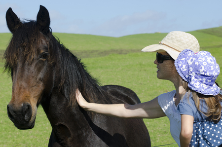 pat: Mother and daugther pat a black horse in a horse farm Stock Photo