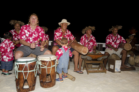 tahitian: Portrait of Polynesian Pacific Island Tahitian music group in colorful outfit in play music on tropical beach. Editorial