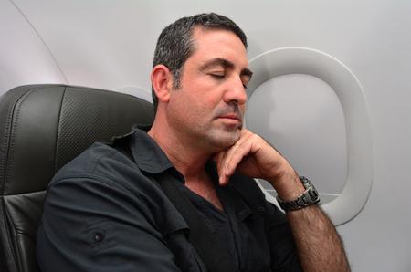 jetliner: Man sleep during flight aboard a jetliner airplane. Stock Photo