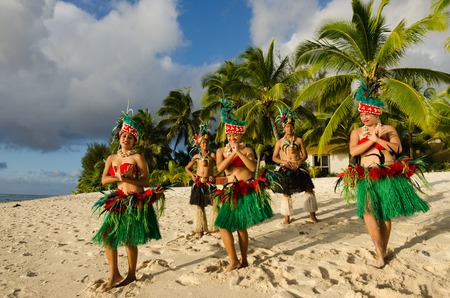 Group portrait of Polynesian Pacific Island Tahitian dance group in colorful costumes dancing on tropical beach with palm trees in the background. (Photo have MR)