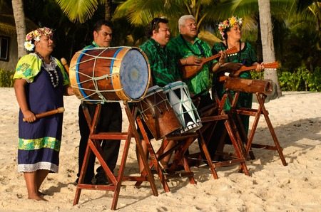 islanders: Group portrait of Polynesian Pacific Islanders band plays Tahitian music on tropical beach with palm trees in the background. Photo have MR