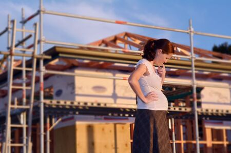 shure: Young pregnant woman worried outside here new home. Concept photo of buy a new home Stock Photo
