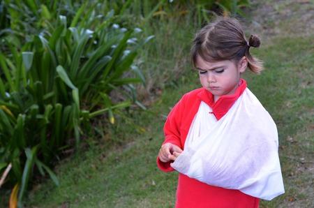 brazo roto: Ni�a triste con un brazo roto al aire libre. Foto de archivo