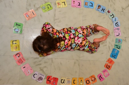jewish home: Little Jewish Israeli girl study the Hebrew alphabet at home.