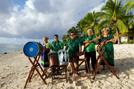 islanders: Group portrait of Polynesian Pacific Islanders band plays Tahitian music on tropical beach with palm trees in the background.