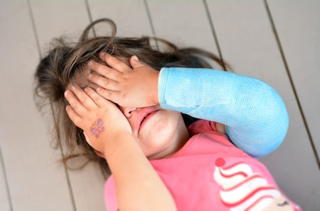 abused girl: Abused little girl with a broken arm covering here face while crying. Concept photo of child abuse, violent in the family,domestic violent, social issues.
