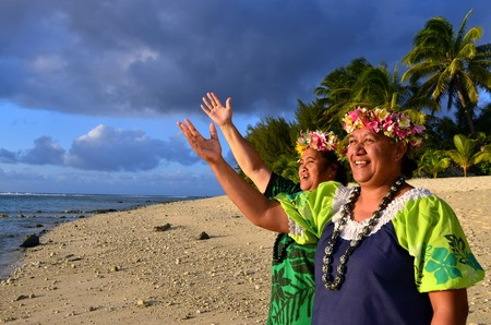 islanders: Portrait of two happy smily mature Polynesian Pacific islanders women on tropical beach with palm trees in the background. Stock Photo