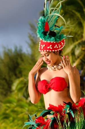 tahitian: Portrait of Polynesian Pacific Island Tahitian female  dancer  in colorful costumedancing on tropical beach with palm trees in the background. Photo have MR Stock Photo