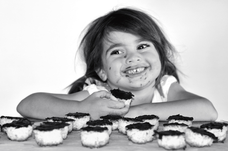 dispersed: Little girl getting caught eating chocolate cookie. Concept photo of Child , children,depression,dispersed, food, health care , diet, eating disorder,bulimia. (BW) copy space Stock Photo