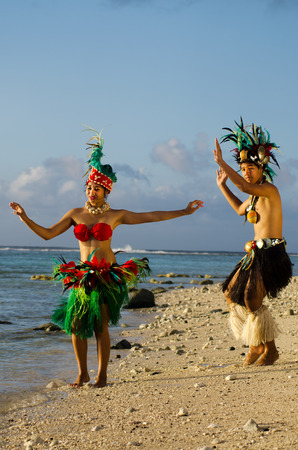 tahitian: Portrait of attractive young Polynesian Pacific Island Tahitian male and female dancers in colorful costumes dancing on tropical beach during sunset. (Photo have MR) Editorial
