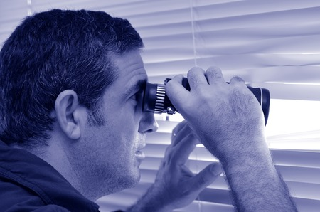 Man (age 35-40 ) looks and searches with binoculars and  looks out through Venetian blinds. Concept photo of curious, spy, nosy man (BW).