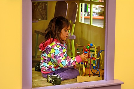 play room: Little girl play with wood  toy in play room. Preschool.