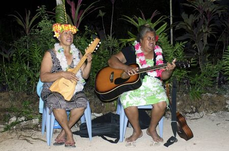 tahitian: Portrait of Polynesian Pacific Island Tahitian mature females sing a song and play music with Ukulele and Guitar on tropical beach in Aitutaki lagoon Cook Islands. Stock Photo