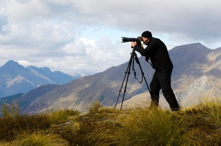 documenting: Professional on location and nature photographer man photographing landscape  outdoor.