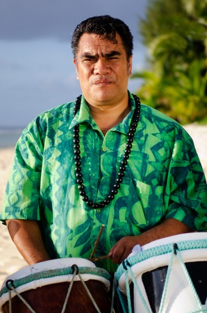 islanders: Portrait of mature Polynesian Pacific islanders man plays Tahitian Music with drums on tropical beach with palm trees in the background. Photo have MR