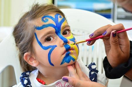 body paint: Niña que consigue su rostro pintado en forma de mariposa. Maquillaje.