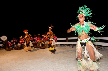 tahitian: Polynesian Pacific Island Tahitian male dancers in colorful costume dancing on tropical beach.