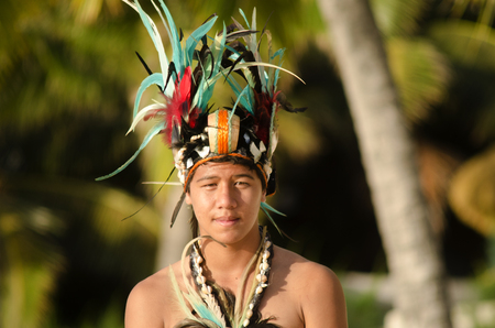 tahitian: Portrait of attractive young Polynesian Pacific Island Tahitian male dancer in colorful costume dancing on tropical beach during sunset. Editorial