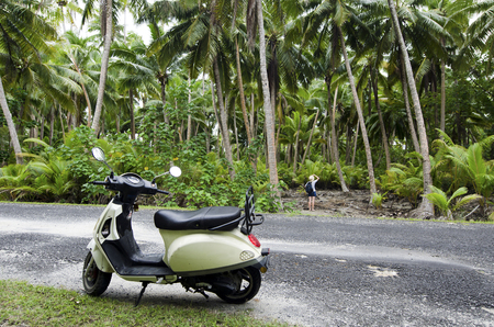drivers license: AITUTAKI - SEP 20:Tourist woman explore the nature with motorbike on Sep 20 2013.Its one of the must popular activity in the Island but Cook Islands Drivers License is required for motorized rental.