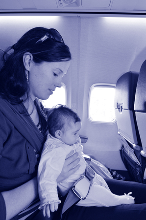 air baby: Mother carry her infant baby during flight.Concept photo of air travel with baby. (BW) Stock Photo
