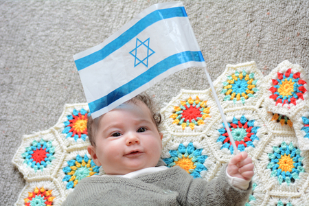 An Israeli newborn baby holding the Israeli flag. Concept photo Israel, Israeli , citizen, patriotism, family, childhood, fertility rate.