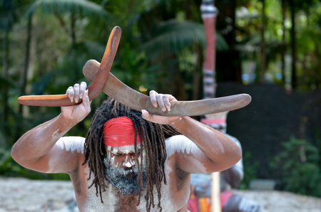 Yugambeh アボリジニ男は、クイーンズランド州、オーストラリアのアボリジニ文化ショーの間にブーメランを保持しています。