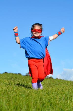 pretend: Superhero child girl against dramatic blue sky background with copy space. concept photo of Super hero, girl power, play pretend, childhood, imagination.