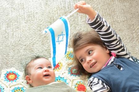 israeli: Two Israeli sisters holding the Israeli flag. Concept photo Israel, Israeli , citizen, patriotism, family, childhood, fertility rate.. Stock Photo