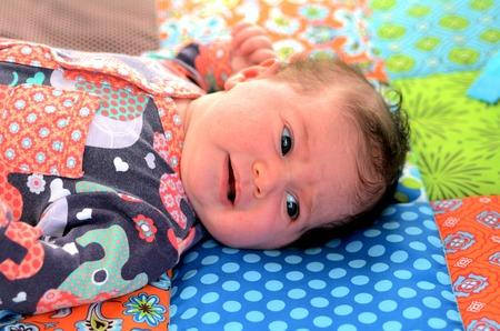 floor mat: Portrait of a Newborn baby awake on baby floor mat. Concept photo of newborn, baby, mother, motherhood, parenting and lifestyle