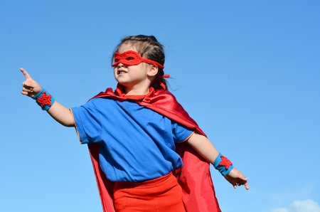 pretend: Superhero child (girl) fly against dramatic blue sky outdoor background with copy space. concept photo of Super hero, girl power, play pretend, childhood, imagination.