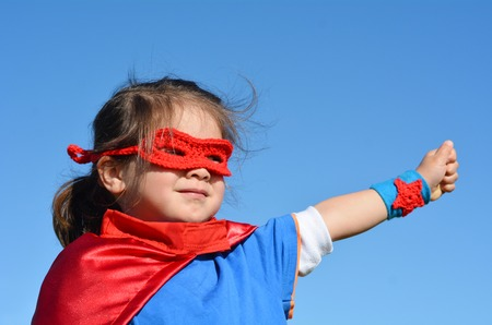 pretend: Superhero child (girl)  against dramatic blue sky background with copy space. concept photo of Super hero, girl power, play pretend, childhood, imagination. Stock Photo