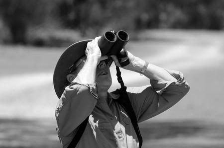 gold coast australia: Mature woman birdwatching watching through binoculars in Coombabah Lake Conservation Park IN Gold Coast, Australia (BW)