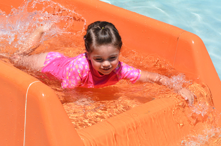 space age: Child (girl age 04) play with water in water park.Concept photo with copy space