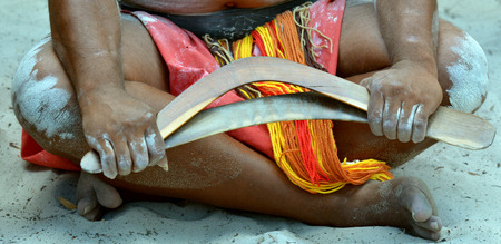 boomerangs: Yugambeh Aboriginal man sit and holds boomerangs during Aboriginal culture show in Queensland, Australia. Stock Photo