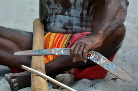 australian ethnicity: Yugambeh Aboriginal man sit and holds boomerang and didgeridoo during Aboriginal culture show in Queensland, Australia.