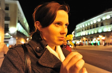 spanish woman: Spanish woman holding a flower in Plaza del Sol (Puerta del Sol) central square in Madrid Spain at night.