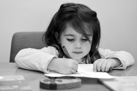 Portrait of a little cild ( girl age 4 ) concentrated while drawing and painting a picture. (BW)