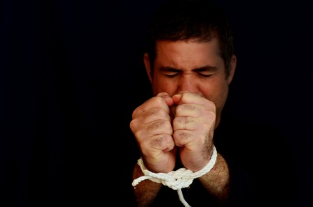 slave labor: Missing kidnapped, abused, hostage, victim man with hands tied up with rope in emotional stress and pain, afraid, restricted, trapped, call for help, struggle, terrified, locked in a cage cell. Stock Photo