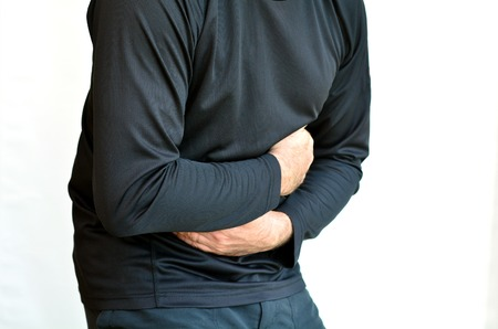 constipation symptom: Man with stomach pain standing against white background. Torso and hands. Concept photo of healthcare and Medical