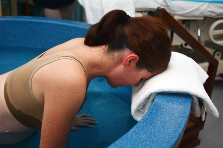 nacimiento de bebe: La mujer embarazada durante el parto en el agua natural.