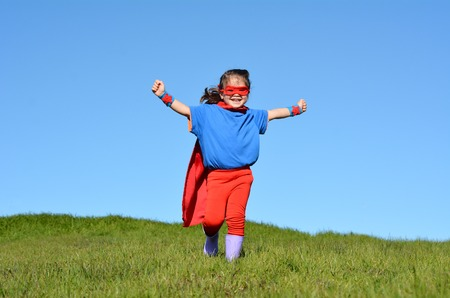 pretend: Superhero child (girl) runs against dramatic blue sky outdoor background with copy space. concept photo of Super hero, girl power, play pretend, childhood, imagination.