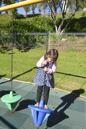 children play: Little girl play in modern children toy playground in park.