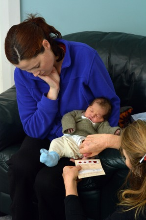 headings: AUCKLAND - JUNE 09 2014:Midwife take blood sample from a newborn during metabolic screening test.Newborn screening samples are collected from the infant between 24 hours and 7 days after birth.